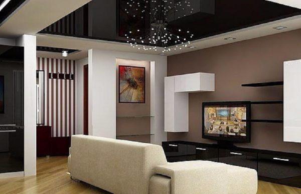 Интерьер большой гостиной с темным натяжным потолком